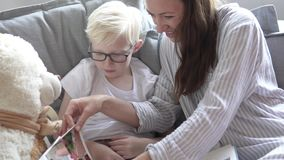 Cute mom and son insert photos into the boy is children`s photo album