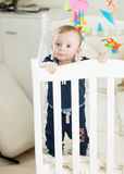Cute 9 month old boy standing in white wooden crib Royalty Free Stock Image
