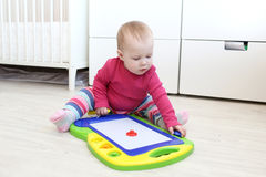 Cute 10 months baby girl plays Magnetic Childrens Drawing Board Stock Image