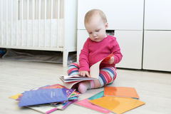 Cute 10 months baby girl reads books at home Royalty Free Stock Images