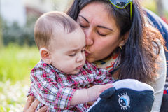 Cute 6 months baby receiving kiss by mum Royalty Free Stock Photography