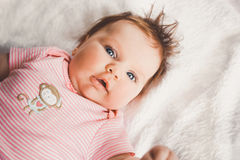 Cute 3 months old baby girl in pink lying down on a white bed at home looking at camera. Big open eyes. Infant napping Stock Photography