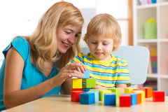 Cute mother and child boy play together with educational toys Stock Photo