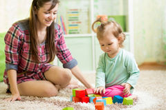 Cute mother and child girl playing together indoor Stock Images