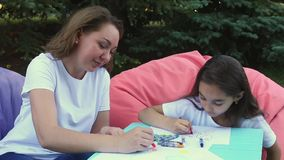 Cute mother and daughter drawing sitting in park at summer day. stock footage