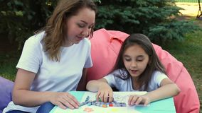 Cute mother and daughter drawing sitting in park at summer day. stock video