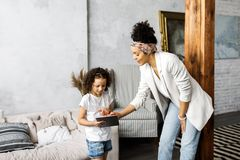 A cute mother and daughter talk and look at the tablet while standing in the living room.  royalty free stock images