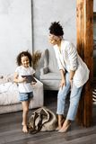 A cute mother and daughter talk and look at the tablet while standing in the living room.  stock image