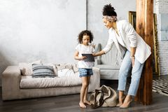 A cute mother and daughter talk and look at the tablet while standing in the living room.  stock photo
