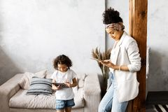 A cute mother and daughter talk and look at the tablet while standing in the living room.  royalty free stock photography