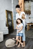A cute mother and daughter talk and look at the tablet while standing in the living room.  royalty free stock image