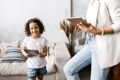 A cute mother and daughter talk and look at the tablet while standing in the living room.  royalty free stock photos