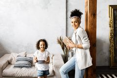 A cute mother and daughter talk and look at the tablet while standing in the living room.  stock photography