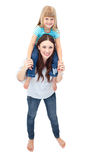 Cute mother giving her daughter piggyback ride Royalty Free Stock Image
