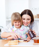Cute mother helping her daughter in the kitchen Stock Photography