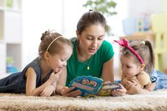 Cute mother and her two daughters children reading story together royalty free stock image
