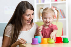 Cute mother and her daughter child playing together indoor Royalty Free Stock Images