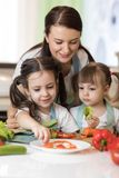 Cute mother and her kids making vegetable salad. Cute mom and her kids making vegetable salad Stock Image
