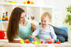 Cute mother and her son playing together indoor Royalty Free Stock Photography