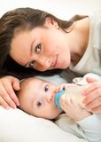 Cute mother at home feeding baby son with a milk Stock Photo