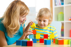 Cute mother and kid boy play together with educational toys Royalty Free Stock Photography