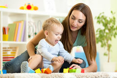Cute mother and kid boy playing together indoor Stock Images