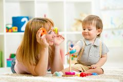 Cute mother and kid boy playing together indoor Royalty Free Stock Image