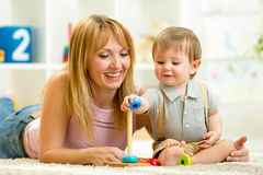 Cute mother and kid playing together indoor Royalty Free Stock Photo