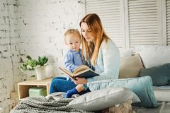 Cute Mother Reading a Book to her Son at Home Stock Photography