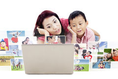 Cute mother and son looking at photos on laptop Royalty Free Stock Photos