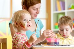 Cute mother teach her kids to paint Royalty Free Stock Photos