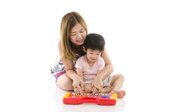Cute mother teach her son kid to play electrical toy piano Stock Photo