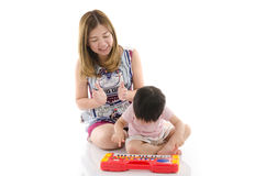 Cute mother teach her son kid to play electrical toy piano Royalty Free Stock Image