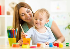 Cute mother teach her son to paint Stock Images