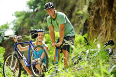 Cute mountain bike couple. Cute adorable couple smile and are happy with mountain bike outdoors Royalty Free Stock Images