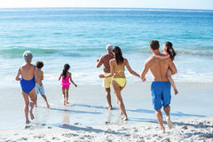 Cute multi generation family running in the sea Royalty Free Stock Image