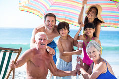 Cute multi generation family setting up their umbrella Stock Images