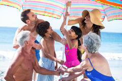 Cute multi generation family setting up their umbrella Royalty Free Stock Images