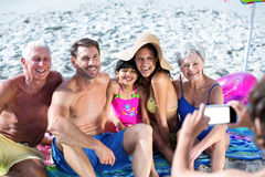 Cute multi generation family taking a picture. On the beach Stock Photo