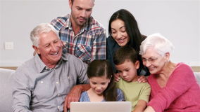 Cute multi generation family using laptop on the couch. In the living room stock footage