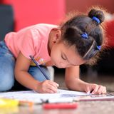 Cute multiracial small girl drawing on a coloring book. While lying on the floor Royalty Free Stock Photography