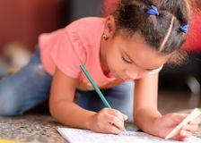Cute multiracial small girl drawing on a coloring book. While lying on the floor royalty free stock images