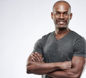 Cute muscular grinning man with folded arms. Single handsome fit grinning young Black adult with shaved head and folded muscular arms over gray background with Stock Photo