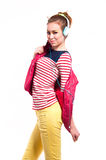 Cute music girl. Pretty young woman isolated on white wearing bright colordul clothes like pink vest, yellow jeans, stripped red white blue shirt, listening to Stock Photography