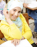 Cute Muslim arabic girl sitting on the chair. And holding pencil - at school Stock Photo