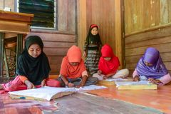 Cute Muslim girls drawing pattern on Batik fabric. Krabi, Thailand - May 2, 2015: Cute Muslim girls drawing pattern on Batik fabric for painting in their home in Stock Photo