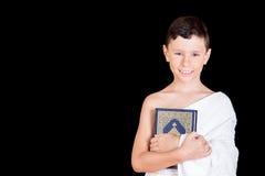 Cute Muslim Kid holding Quraan While Wearing Ihram During Hajj Stock Images