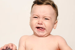 Cute naked baby boy crying. Little child in pain, suffering, teething, refusing and crying. Cute sad baby throwing a tantrum. Baby wants up in the arms to be Stock Images