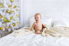 Cute naked baby girl sitting on bed at bedroom. Christmas. Royalty Free Stock Photography