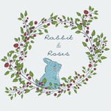 Cute natural frame from branches of a rose with a blue rabbit. Royalty Free Stock Photos